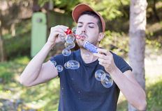 Young man makes soap bubbles Stock Images