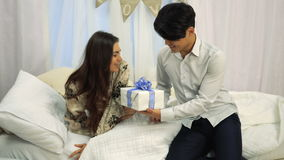 Young man makes a surprise for his girlfriend on Valentine`s Day while she sleeps. Congratulations loved one on Valentine`s Day stock video footage