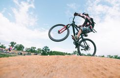 A young man makes tricks on a mountain bike. A cyclist jumps on a bike. A young man makes tricks on a mountain bike. cyclist jumps on a bike royalty free stock image