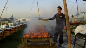 Young man prepares BBQ in large quantity. Young man making BBQ on commercial level for large number of people.nVideo is shot during an event organized in PAF stock video