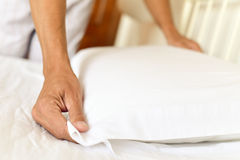 Young man making the bed. Closeup of a young caucasian man arranging the pillow as he is making the bed royalty free stock photo