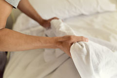 Young man making the bed Stock Images