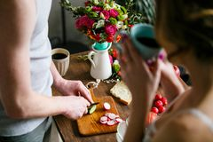 Young man making breakfast together with his girlfriend stock images