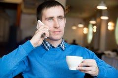 Young man making call at breakfast royalty free stock photo