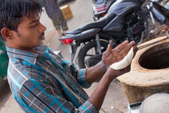 Young man making chapati at streetside restaurant in Delhi, Indi Stock Images