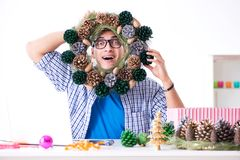 The young man making christmas decoration from cones royalty free stock image