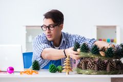 The young man making christmas decoration from cones royalty free stock images