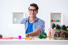 The young man making christmas decoration from cones stock photos