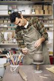 Young man making pottery in workshop. Young man making and decorating pottery in workshop Royalty Free Stock Photos