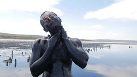 Young Man Making Face Mask with Black Medical Mud at the Lake of Salt Water. Salty Black Dirt Is Good For People With