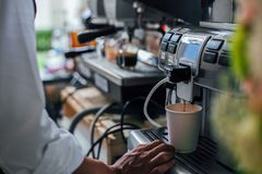 Young man is making fresh coffee with coffee machine. Self-service coffee machines offer consistent quality coffee in office royalty free stock images
