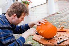 Young man making halloween pumpkin Stock Image