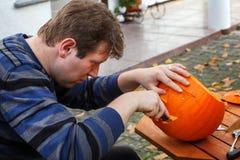 Young man making halloween pumpkin Stock Photo