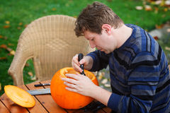 Young man making halloween pumpkin Stock Photos