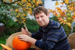 Young man making halloween pumpkin Stock Images
