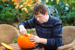 Young man making halloween pumpkin Royalty Free Stock Photo
