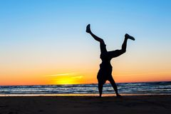 Young man making handstand on the beach. Multicolored sunset bac Stock Photos