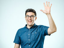 Young man making high five gesture. Isolated on gray background royalty free stock image
