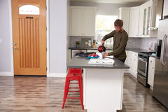 Young Man Making Hot Drink In Apartment Kitchen Royalty Free Stock Images