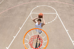 Young Man Making Jump Shot on Basketball Court stock image