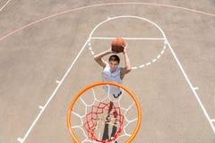 Young Man Making Jump Shot on Basketball Court Stock Image