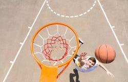 Young Man Making Lay Up Shot on Basketball Net Stock Image