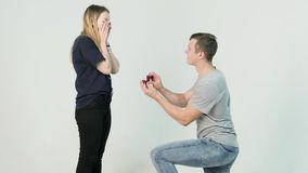 Young man making marriage proposal to his girlfriend. Man is kneeling to the young woman proposing to the girl to get. Married on white background 4K stock video footage