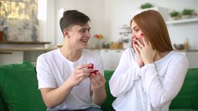 Young man making marriage proposal to surprised woman with ring in red gift box sitting on sofa, amazed happy woman. Marriage Proposal - A man gives a ring to a stock video footage