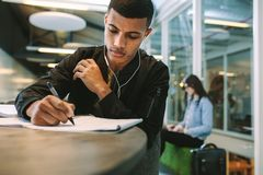 Student preparing for exams at university library. Young man making notes on book. Male student preparing for exams at university library royalty free stock photos