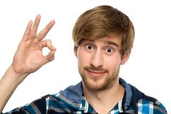 Young man making OK sign. Young man over white background Stock Image
