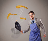 Young man making pancakes Royalty Free Stock Image