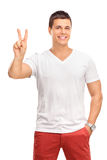 Young man making a peace hand gesture Stock Images