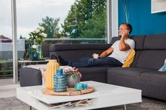 Young man making a phone call while drinking coffee on the couch stock image