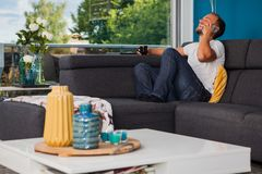 Young man making a phone call and laughing loudly on the couch stock photo