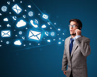 Young man making phone call with message icons Royalty Free Stock Image