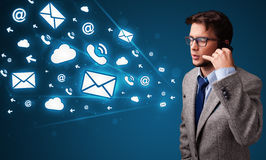 Young man making phone call with message icons Stock Image
