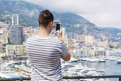 Young man  making photos  at Monte Carlo harbour in Monaco. Azur coast. Royalty Free Stock Photo