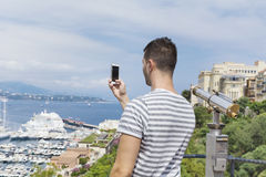 Young man  making photos  at Monte Carlo harbour in Monaco. Azur coast. Stock Image