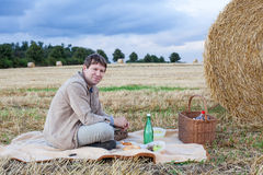 Young man making picnic on hay field Royalty Free Stock Photo