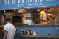 A young man making a pizza in a mobile cafe Royalty Free Stock Image