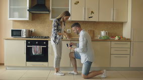 Young man making proposal to his girlfriend in the kitchen at home stock video