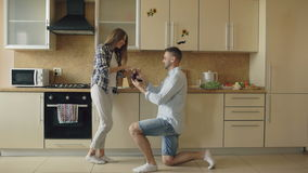 Young man making proposal to his girlfriend in the kitchen at home stock video footage