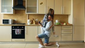 Young man making proposal to his girlfriend in the kitchen at home Stock Photo