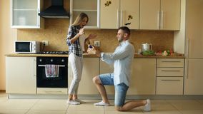 Young man making proposal to his girlfriend in the kitchen at home Stock Photos