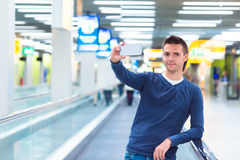 Young man making selfie by cell phone at airport Royalty Free Stock Photos