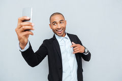 Young man making selfie photo on smartphone over gray background Royalty Free Stock Image
