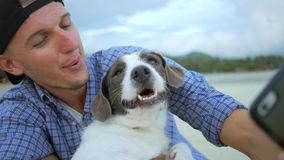 Young Man Making Selfie Portrait With His Dog at the Beach. Thailand. HD Slowmotion.