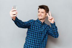 Young man making selfie using smartphone. Young smiling man holding two fingers gesture and making selfie on smartphone stock photos