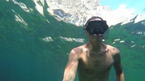 Young man making selfie video underwater. Young man looking for adventure. Underwater selfie video shot stock video