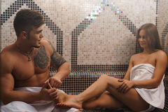 Young man making sexy girl foot massage in sauna Stock Photos